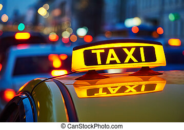 taxi sign on car at evening in the city street