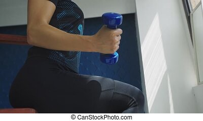 Close up side view of fitness woman in black sportswear exercising with dumbbells in gym