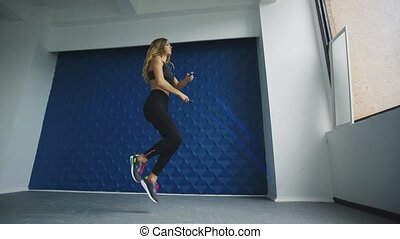Side view of healthy fit woman jumping with jumping rope in a fitness club or gym
