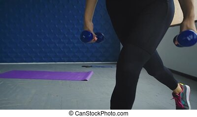Close up of woman hands holding dumbbells at gym. Woman works with small dumbbells
