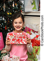 Childlike Joy - Little girl holds a gift from her...
