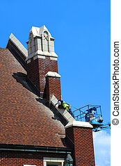 Church Upkeep - Construction worker, wearing a harness and...