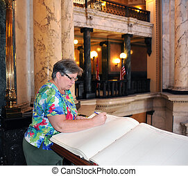 Capital Guest Book - Visitor signs guest book inside the...
