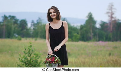 Beautiful girl in the black short dress on the green field.
