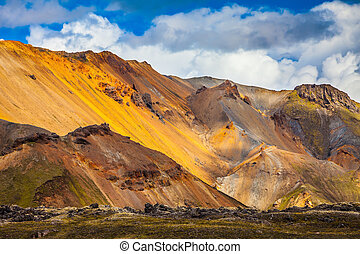Bright, multi-colored rhyolite mountains - yellow, orange,...