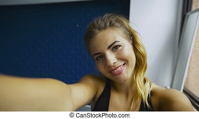 Smiling playful young sportswoman in black top taking selfie...