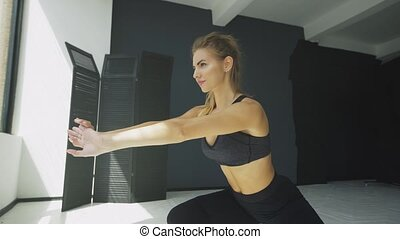 Side view portrait of a young blonde woman doing squats while standing in front of window at gym