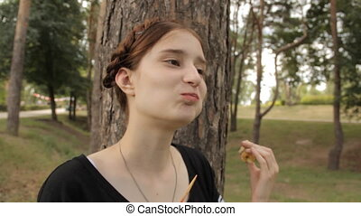 The girl eats candy apple and looks to the camera.