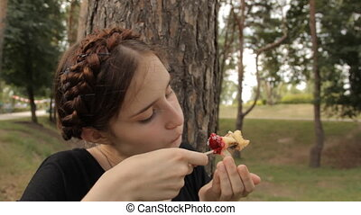 Beatiful girl removes an apple from the stick.