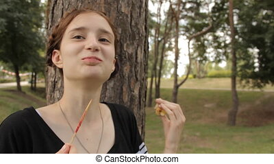 Hipster girl eats candy apple and laughs.