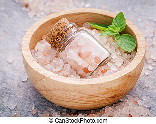 Closeup Himalayan pink salt in wooden bowl and bottle with...