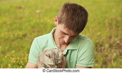 Guy holds a gray British cat.