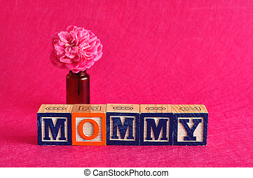 Mommy - The word mom spelled with alphabet blocks against a...