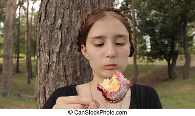 Teenager girl finds a rotten portion of apple.
