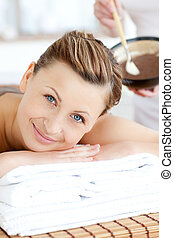 Smiling woman enjoying a mud treatment in a Spa center