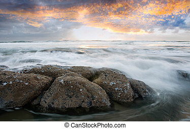 Ebb Tide - Rough ocean water moving swiftly over jagged...