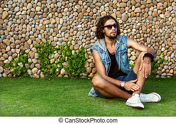 fashion man in sunglasses and jeans clothes sits on grass near palms and smiling Vogue