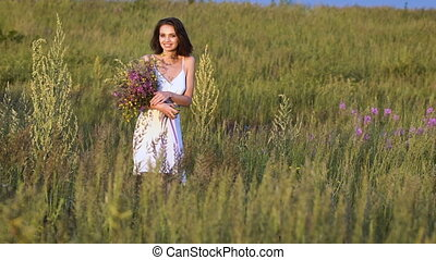 One young woman walking on green field with flower bunch and...