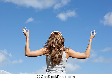 Blond woman punching the air against blue sky