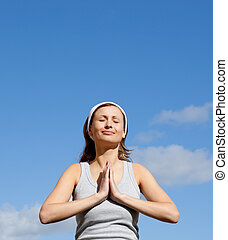 Radiant woman meditating against a blue sky - Portrait of a...
