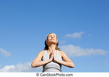 Relaxed woman meditating against a blue sky