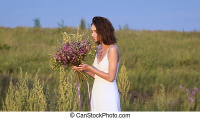 One young woman standing on green field smelling flower bunch