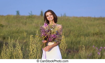 One young woman standing on green field with flower bunch...