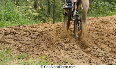 Cyclist rides through the forest, overcoming obstacles, slow...