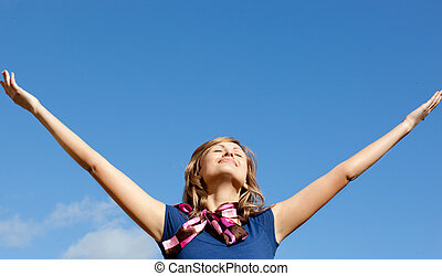 Smiling  blond woman punching tha air against blue sky