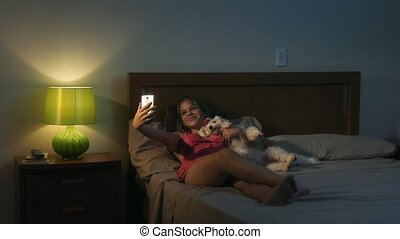 Woman And Dog In Bed Taking Selfie With Phone At Night -...