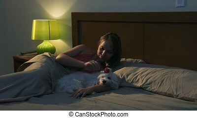 Woman Stroking Dog In Bed Sleeping At Night - People and...