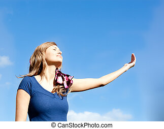 Attractive  blond woman against blue sky