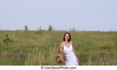 One young woman standing on green field throwing a flower bunch
