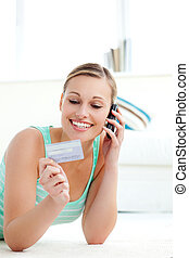 Laughing woman holding a credit card at home