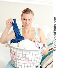 Unhappy woman doing her laundry