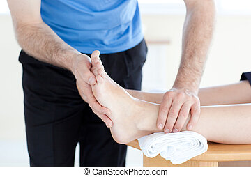 Close-up of a physical therapist giving a foot massage in a...