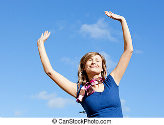 Bright blond woman punching tha air against blue sky