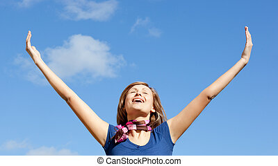 Happy blond woman punching tha air against blue sky