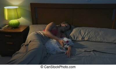 Woman Stroking Dog In Bed At Night Sneezes For Allergy -...