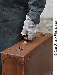 immigrant with old leather suitcase and broken gloves - poor...
