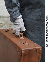 poor immigrant with old leather suitcase during the trip...