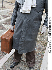 poor immigrant with old leather suitcase and filthy dress