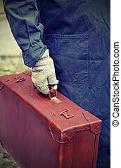 immigrant with old leather suitcase and the unstitched glove...