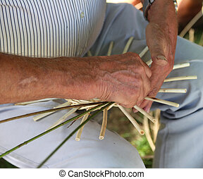 big hands expert craftsman while creating a basket - big...