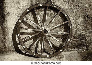 Old wagon wheel - An old wagon wheel,leans against a stucco...