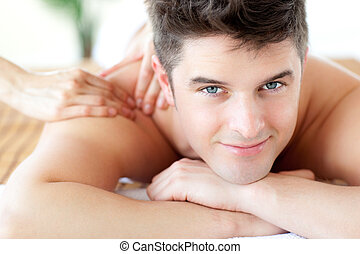 Cute man enjoying a back massage in