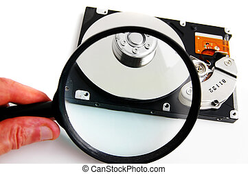 Hand holding a magnifying glass over a harddrive
