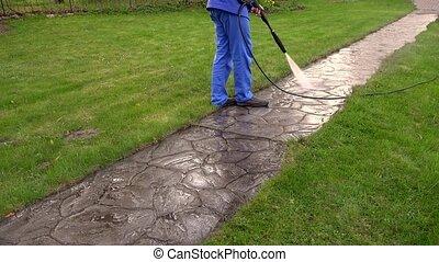 Man Washing Concrete Path With Pressure Washer Garden...