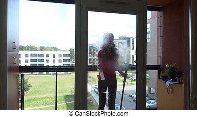 young pretty woman spray chemical and wipe window at clients...