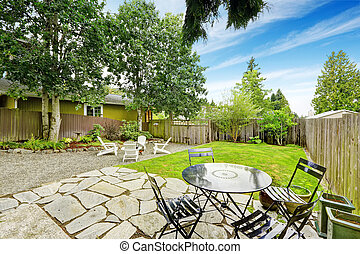 Fenced back yard with patio area and white adirondack chairs.